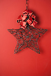 USA, California, La Quinta, Wire star and bow against red background