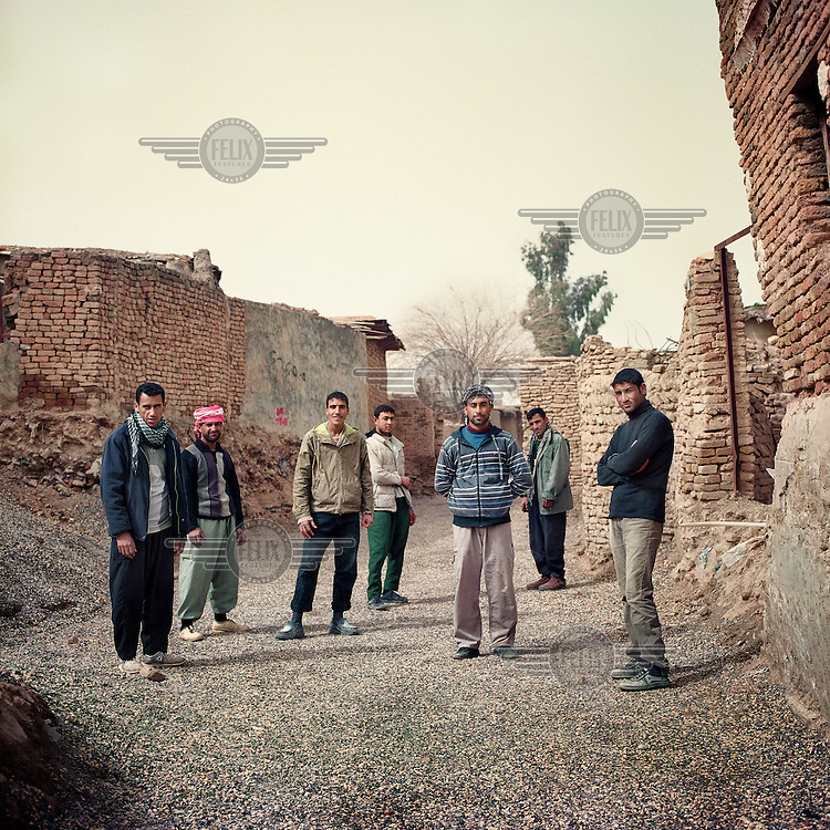 A group of men stand among the semi ruined dwellings within the ancient Citadel of Arbil in Iraq. The Citadel is an inhabited mound in the centre of the modern Iraqi city of Erbil, which is said to be one of the oldest, continually inhabited places in the world. Earliest traces of habitation on the mound date back to the 5th millennium BC, possibly earlier. The city of Erbil, the fourth biggest in Iraq, is today the capital of Iraqi Kurdistan. .Since 2007 the High Commission for Erbil Citadel Revitalisation (HCECR) has been in charge of the Citadel complex and is carrying out major reconstruction efforts since moving out all remaining residents. It is hoped that 50 families will move back into the Citadel once renovation work and archeological digs have been completed. .