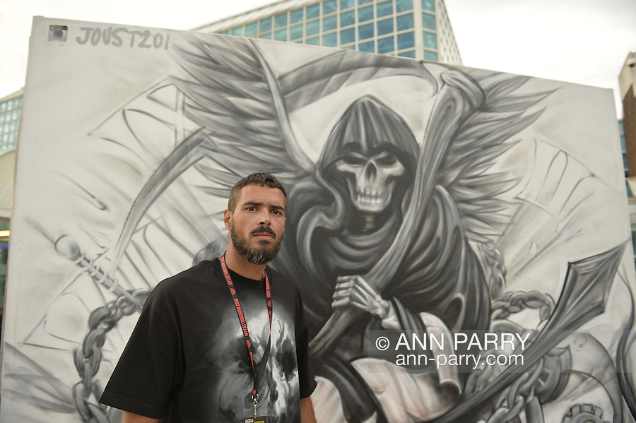Garden City, New York, USA. 14th September 2014. DAN AZACETA, aka JOUST201, from New Jersey, is a graffiti artist creating a black and white outdoor mural of the Grim Reaper, at the United Ink Flight 914 tattoo convention at the Cradle of Aviation museum of Long Island.