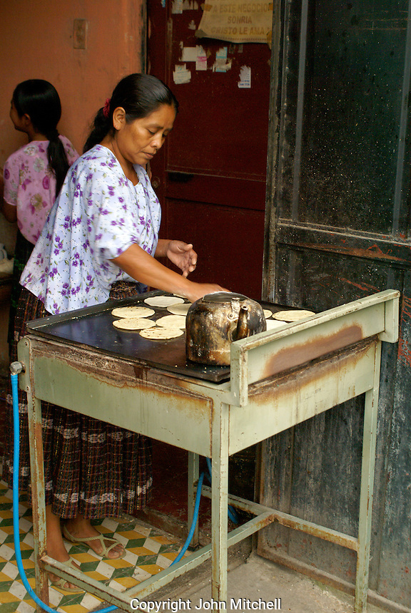 Maya woman cooking corn tortillas on a grill in Coban, Alta Verapaz, Guatemala.