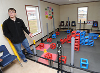 STAFF PHOTO ANDY SHUPE - Sponsor Stephen Needham shows the space his robotics students use to practice for competition Thursday, Dec. 18, 2014, that is housed in a mobile classroom on the north side of Southwest Junior High School in Springdale.