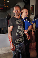 Switzerland. Geneva. Paquis neighborhoo. A bald police officer holds the left arm of a black african man from Guinea. The man was hurt during a fight with another african man. He is bleeding blood from his nose and right arm. He wears a black tshirt with the words: Fight for your right to party. He will be left free after refusing any medical assistance. 8.07.12 © 2012 Didier Ruef..