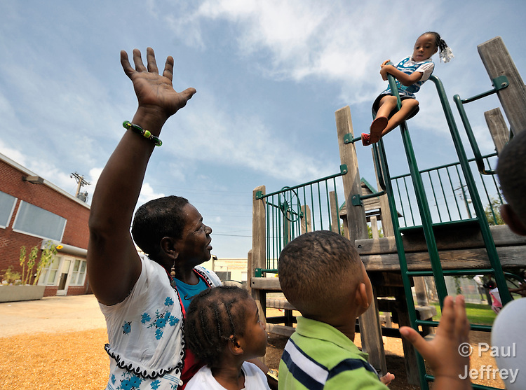 A staff member waves her arms, enthusiastically helping children enjoy their play in a day care center run by the Lessie Bates Neighborhood House in East St. Louis, Illinois.