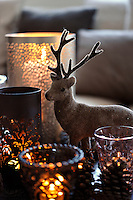 Detail of one of the flocked reindeer ornaments that glitter on the candlelit coffee table in the living room