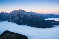 Watzmann (2713m) rises above fog inversion layer at sunrise, viewed from summit of Jenner, Berchtesgaden national park, Bavaria, Germany
