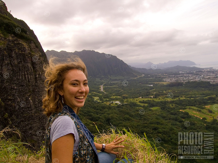 A young local woman at the windy Pali Lookout, with Kane'ohe in the distance, O'ahu.