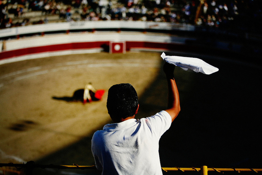 A spectator cheers matador Omar Villasenor during a performance at Plaza Monumental, Tijuana, Baja de California, MX, July 1, 2007. Though badly injured during the match, Villasenor continues to fight the bull winning the support of the crowd. The white handkerchief represents an excellent performance, and that the fan wishes the judge to grant the bullfighter an ear. After the match the judge deemed the match worthy of two ears, the highest honor for the bullfighter..