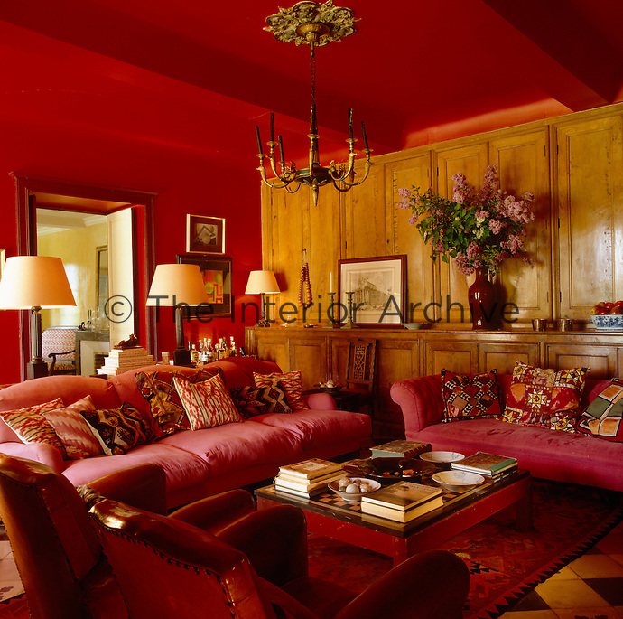 A built-in cabinet of elm lines one wall of this red sitting room which is furnished with large pink sofas scattered with brightly patterend cushions