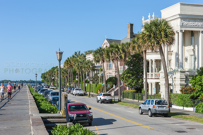 People walk and jog across from historic antebellum mansions on Battery Row, in Charleston, South Carolina.