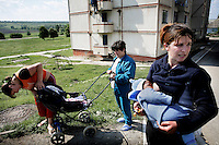 Viorica Belaia breast feeds her baby while standing outside an apartment with two friends. She works at the the Bucuria vineyard in South Moldova where she is paid about 15 GBP each month.