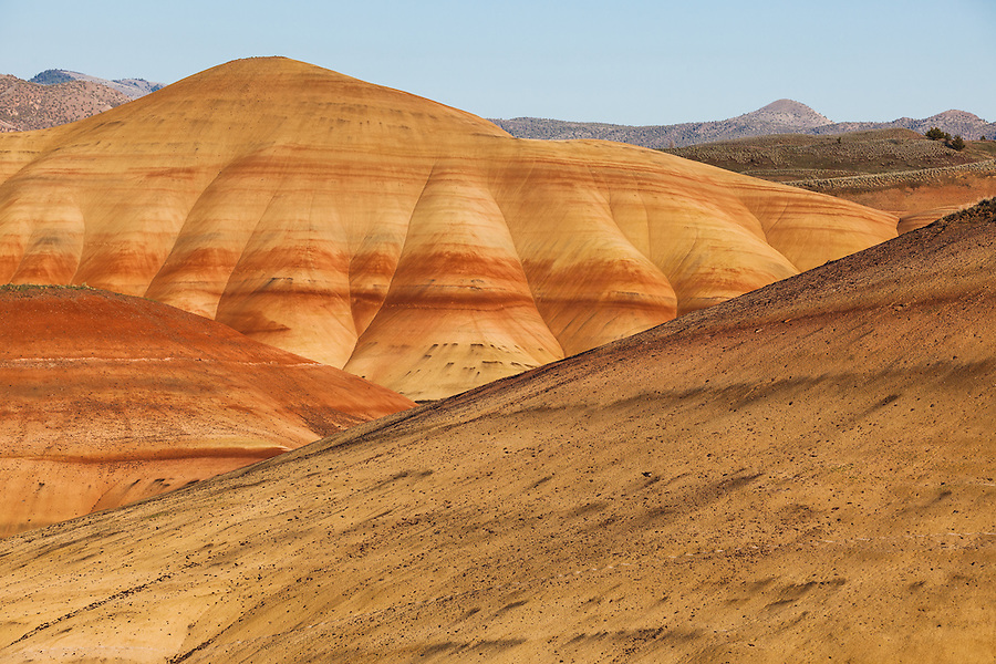 A clear blue sky is seen above a red and yellow hill in the Painted Hills section of the John Day Fossil Beds National Monument in Wheeler County, Oregon.