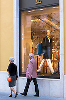 Couple walking past Louis Vuitton shop in Residenzstrasse in  Munich, Bavaria, Germany