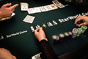 A poker player reveals his card on the poker table at the Galaxy Macau Hotel in Macau, China.
