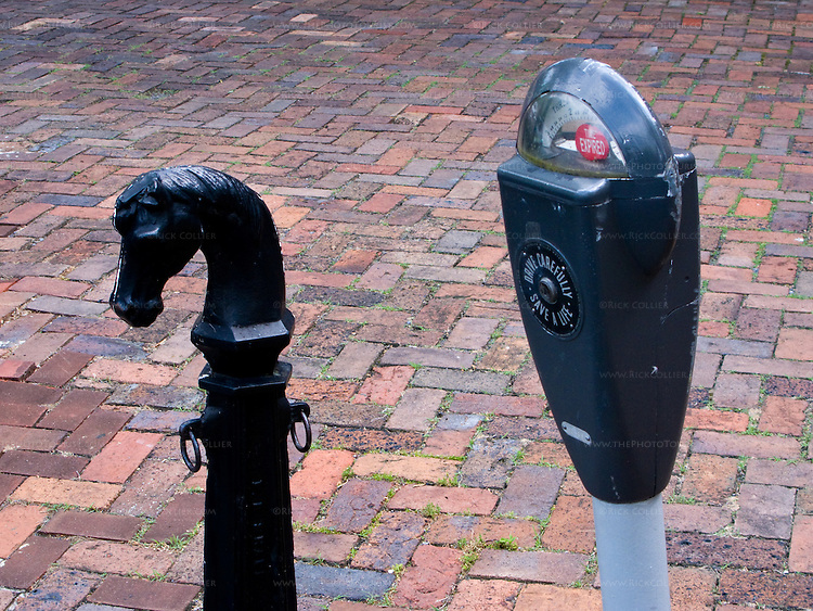 Evolution in hitching posts:  An antique horse hitching post stands next to a new parking meter in the town's historic downtown.  Winchester Virginia, USA.  © Rick Collier
