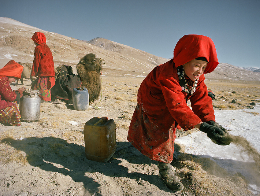 Right, Tella Bu. Every morning, the girls from the Khan's camp are in charge of getting water all throughout winter in sub zero temperature. They have to dig hole in the ice to hope and find the spring that always freezes overnight..Qyzyl Qorum campment, Abdul Rashid Khan's camp (leader of the Afghan Kyrgyz). .Winter expedition through the Wakhan Corridor and into the Afghan Pamir mountains, to document the life of the Afghan Kyrgyz tribe. January/February 2008. Afghanistan