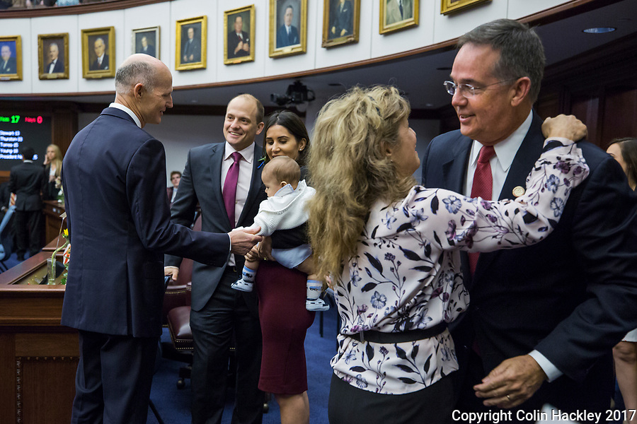 TALLAHASSEE, FLA. 3/7/17-It is not all politics during opening day as old acquaintances are renewed. Gov. Rick Scott, left, greets Sen. Jose Javier Rodriguez, D-Miami, wife Sonia and their son Javier, age six months, as former Rep. Michelle Rehwinkel Vasilinda greets Chief Financial Officer Jeff Atwater right, of the legislative session at the Capitol in Tallahassee.<br /> <br /> COLIN HACKLEY PHOTO