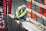 A worker disconnects a crane's chain and cable from a piece of equipment  at the Duboistown Bridge.