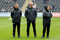 ( L-R ) Billy Reid, assistant manager for Swansea, Alan Curtis, assistant coach for Swansea and Head physiotherapist, Kate Rees watch the players warm up during the Sky Bet Championship match between Swansea City and Preston North End at the Liberty Stadium, Swansea, Wales, UK. Saturday 11 August 2018