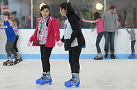 NWA Democrat-Gazette/DAVID GOTTSCHALK  Amisaday Hurbines (left), 10, holds hands with Jocely Alvarado, 10, as they skate Friday, March 23, 2018, during the Frozen Friday skating event at the Jones Center in Springdale. Animated movie princess characters Elsa and Anna visited with skaters as part of the Spring Break Week 2018  activities at the center.