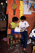 Vila Prudente, Sao Paulo, Brazil. Two young girls in their shanty town favela home looking at a mathematics text book.
