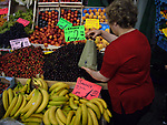 A woman sells fruit at a market in Kreuzberg close to the route of where the Berlin Wall ran and which is being slated for redevelopment and regeneration. The Wall divided Berlin and Germany for 29 years from 1961. A popular uprising took place in East Germany in 1989 and lead to the end of the Cold War and the re-unification of Germany after which Berlin became the nation's capital city once more.