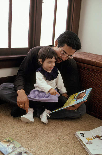 Berkeley CA Girl, age eighteen months, pointing out things in book to Latino father at home