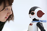 """A woman looks into the eyes of a communication robot called """"Robi"""" during a press preview for """"Robi cafe"""" where visitors can interact with the robots while enjoying meals and drinks in Tokyo, Thursday, January 15, 2015. The robot can be built by assembling parts sent along with a weekly magazine by Deagostini. The cafe will open from January 16 until February 8. (Photo by Yuriko Nakao/AFLO)"""