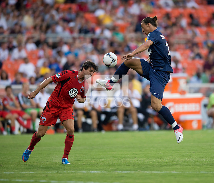 Zlatan Ibrahimovic (18) of Paris Saint-Germain FC takes control of the ball in front of Dejan Jakovic (5) of D.C. United during the game at RFK Stadium in Washington, DC.  Paris Saint-Germain FC tied D.C. United, 1-1.