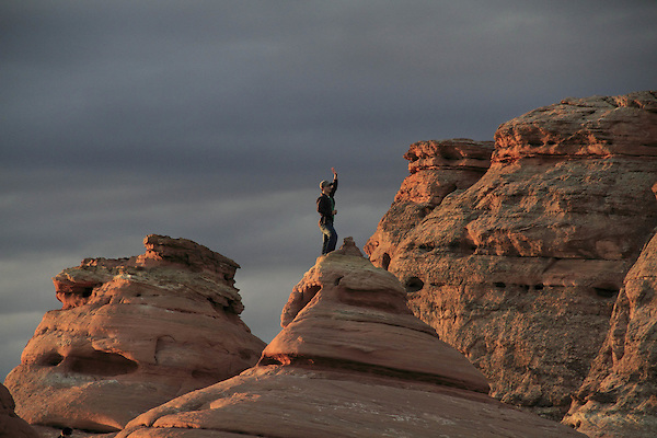 Man waving to friends at sunrise in Arches National Park, Moab, Utah, USA. .  John offers private photo tours in Arches National Park and throughout Utah and Colorado. Year-round.