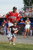 "Batavia Muckdogs left fielder Jhonny Santos (32) takes the field with a young ""Stars of the Game"" participant before a game against the Brooklyn Cyclones on July 4, 2016 at Dwyer Stadium in Batavia, New York.  Brooklyn defeated Batavia 5-1.  (Mike Janes/Four Seam Images)"