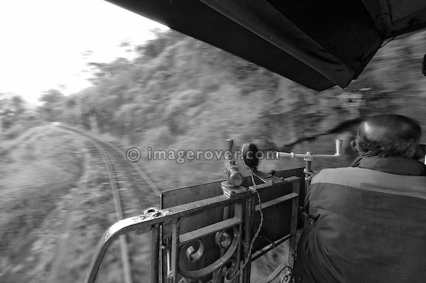 Train crew of the Nilgiri Mountain Railway (steam train). Train descending through the Nilgiri Mountains from Coonoor to Mettupalayam. Part of the journey is managed only by a rack-and-pinion system. India, Tamil Nadu 2005. --- Info: The Nilgiri Mountain Railway (NMR) is the only rack railway in India and connects the town of Mettupalayam with the hill station of Udagamandalam (Ooty), in the Nilgiri Hills of southern India. The construction of the 46km long meter-gauge singletrack railway in Tamil Nadu State was first proposed in 1854, but due to the difficulty of the mountainous location, the work only started in 1891 and was completed in 1908. This railway, scaling an elevation of 326m to 2,203m and still in use today, represented the latest technology of the time. In July 2005, UNESCO added the NMR as an extension to the World Heritage Site of Darjeeling Himalayan Railway.