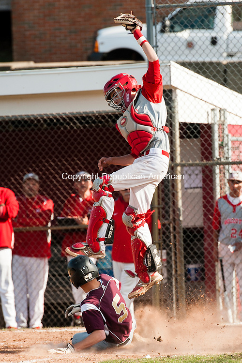 WOLCOTT, CT-28 April 2014-042814EC02-  Sacred Heart's A.J. Petrillo safely slides into home while Wolcott catcher Robert Parazella jumps to get the ball. The run secured the Hearts' victory in the seventh inning. They defeated the Eagles 7-5 in Wolcott Monday afternoon. Erin Covey Republican-American