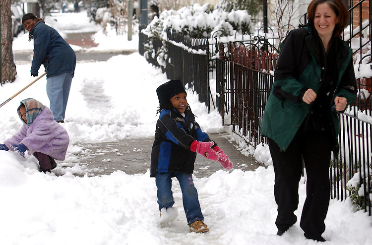 snow5/020703 -- 4 year old Chipo Tucker, center, to fires a snowball at Irene D'Auria of Adams Morgan, while daughter, 4, Francesca D'Auria, gathers snow and mother of Chipo, Vito Tucker, cleans the sidewalk on 5th Street, NE, after Friday' snow fall.
