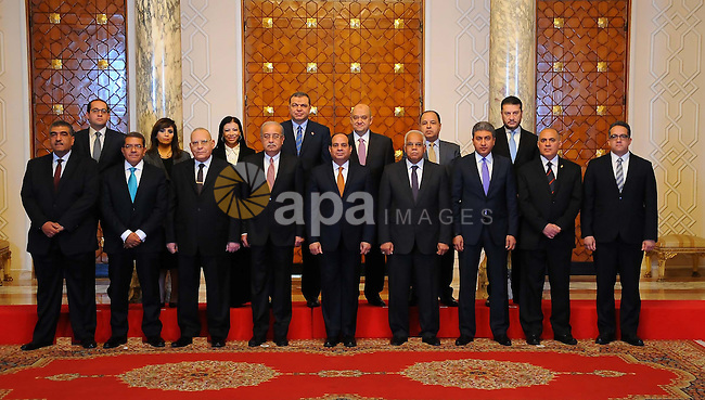 Egyptian President Abdel Fattah al-Sisi poses for a picture with members of the newly appointed cabinet following a meeting in the capital Cairo on March 23, 2016. Sisi swore in 10 new ministers in a cabinet reshuffle, as Egypt struggles to revive an economy battered by falling tourism revenues and foreign investments. The government shake-up -- mainly of economic portfolios -- comes just six months after Sisi inaugurated a new administration led by Prime Minister Sharif Ismail, following the resignation of the previous cabinet after a corruption scandal. Photo by Egyptian President Office