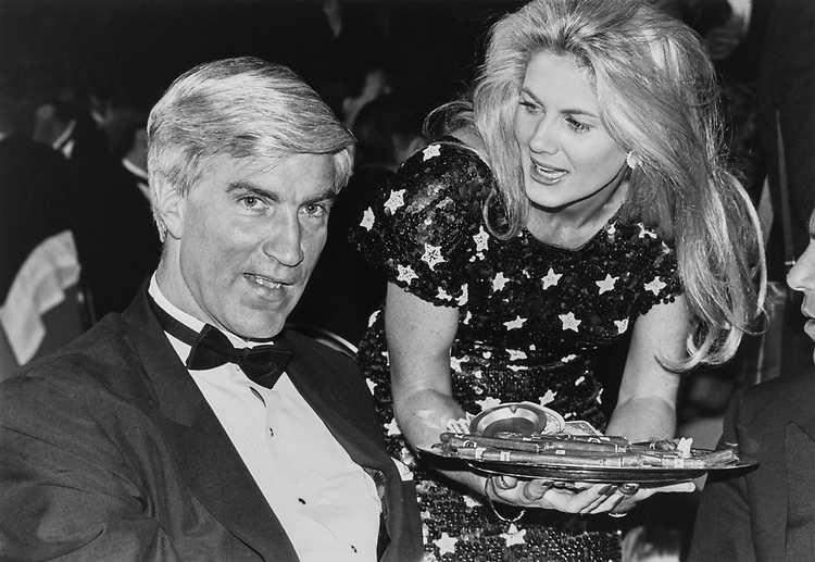 Rep. Tom McMillen, D-Md. offered an after dinner cigar by Jeani Fischer, one of the many hostesses. Other members at the event are Sens. Moran, Tallon, Payne, Edwards and Sarpallus on Nov. 11, 1991. (Photo by Laura Patterson/CQ Roll Call)