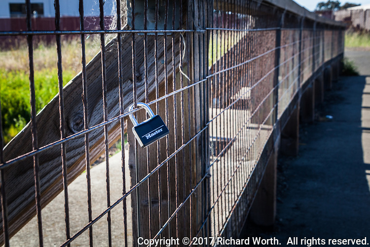A padlock, all by itself,is latched  onto the metal mesh of a foot bridge, apparently not securing anyting, except itself to the wire mesh.  Along a trail at the Martin Luther King Jr. Regional Shoreline in Oakland, California\