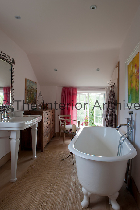 The en suite bathroom is light and comfortable with jute matting laid over the wooden floor