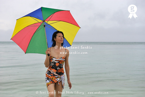 Woman holding umbrella on beach on rainy day (Licence this image exclusively with Getty: http://www.gettyimages.com/detail/88015553 )