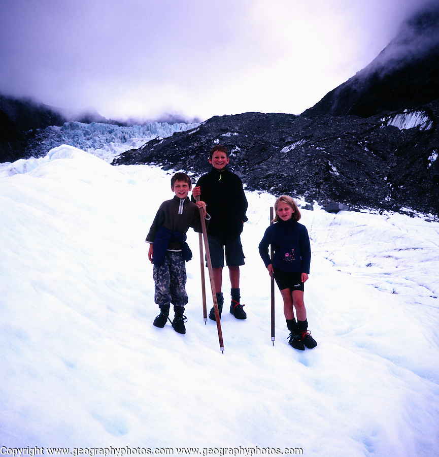 Three children pose for a photo standing on the ice of Fox glacier, New Zealand