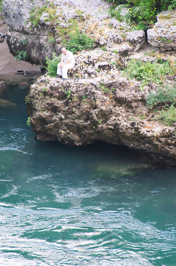 A man sitting on a rock contemplating and looking at the river. Historic town of Mostar. Federation Bosne i Hercegovine. Bosnia Herzegovina, Europe.