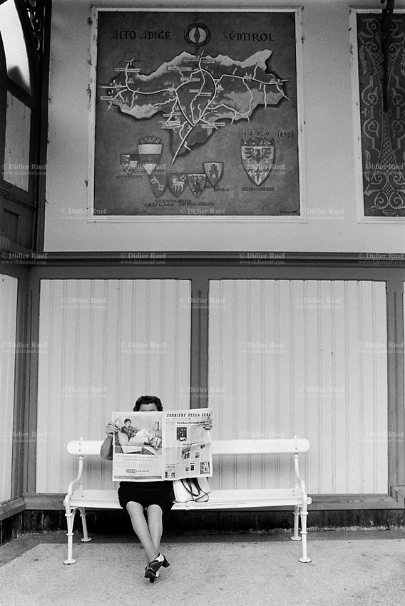 Italy. South Tyrol. Meran. A woman seated on a wooden bench reads the daily newspaper &quot; Corriere della Sera&quot;. <br /> On the wall, amap from South Tyrol with its varius towns and communes. Meran (in italian Merano) is a town and comune in South Tyrol. South Tyrol (German: S&uuml;dtirol; Italian: Sudtirolo, also known by its alternative Italian name Alto Adige) is an autonomous province in northern Italy. 9.08.1999 &copy; 1999 Didier Ruef