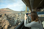 Tourists on tour bus on Ruta de Los Volcanes, Parque Nacional de Timanfaya, national park, Lanzarote, Canary Islands, Spain