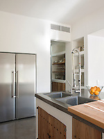 Simple space saving storage has been built in to the walls of the kitchen leaving smooth uncluttered surfaces that gives the kitchen an airy and contemporary feel