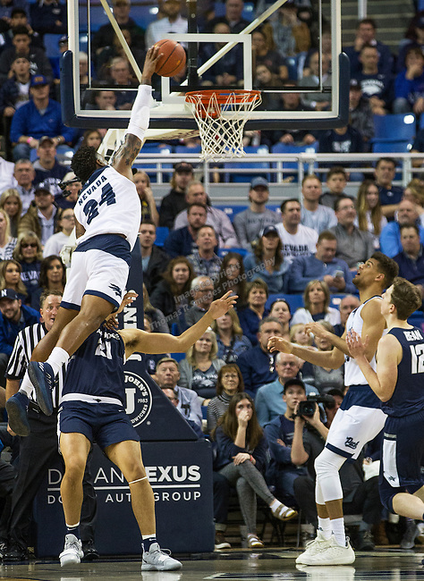 Nevada forward Jordan Caroline (24) attempts to dunks the ball against Utah State in the second half of an NCAA college basketball game in Reno, Nev., Wednesday, Jan. 2, 2019. (AP Photo/Tom R. Smedes)
