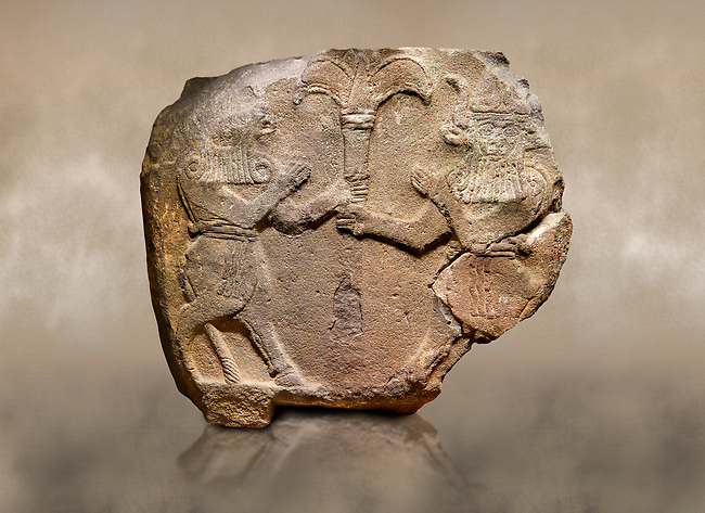 Photo of Hittite monumental relief sculpted orthostat stone panel from Water Gate Basalt, Karkamıs, (Kargamıs), Carchemish (Karkemish), 900-700 B.C.  Anatolian Civilisations Museum, Ankara, Turkey.<br /> <br /> Two bull-men holding the trunk of the tree in the middle. The faces of the figures, having tufts in both temples over the chain, have been depicted from the front direction. The horned figures with bull-like ears and legs have human bodies. <br /> <br /> On a brown art background.