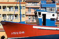Spain, Canary Islands, La Palma, Puerto de Tazacorte: fishing boat, residential buildings