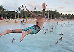 """A girl jumps off the Wall at Waikiki. The """"Wall"""" at Waikiki is a favorite place for tourists and locals to hang-out to see the sunrise, sunsets, swim, surf or just to to meet friends."""