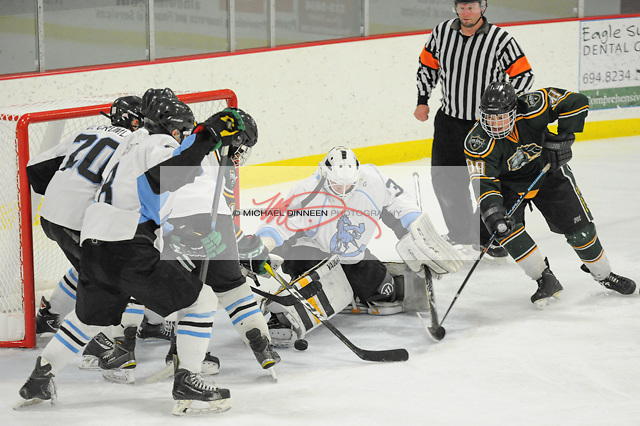 Chugiak goalie Jack Walters and a trio of teammates stop a shot by Colony's Foster Riekana during the Mustangs' 3-2 win at the McDonald Center in Eagle River Tuesday night. Photo for the Star by Michael Dinneen
