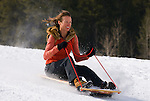 A young woman rides a sled in Jackson, Wyoming.