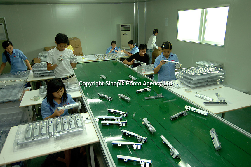Workers inspect freshly moulded and painted parts of a computer casing in Shenzhen China. This factory makes housing for computers, DVD's, mobile phones and computer mouses..